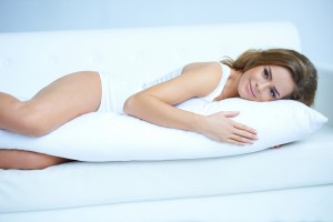 Young pregnant woman laying on white sofa
