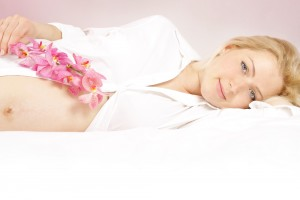 Beautiful pregnant woman in bed with pink orchid flower